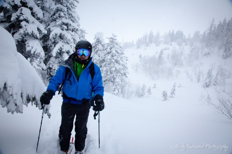 A backcountry skier pauses for breath after making their way up a valley of snow-laden trees near Tokachidake ski area.