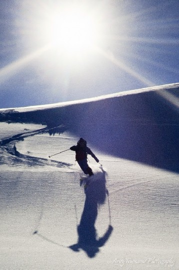 A telemark skier turns down a slope with the sun behind.