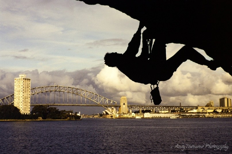 A climbers scales the overhang on Balls head in Sydney Harbour.