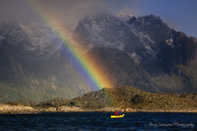 Light rain over a kayaker catches the sun creating a beautiful rainbow in a Nowegian fjord.