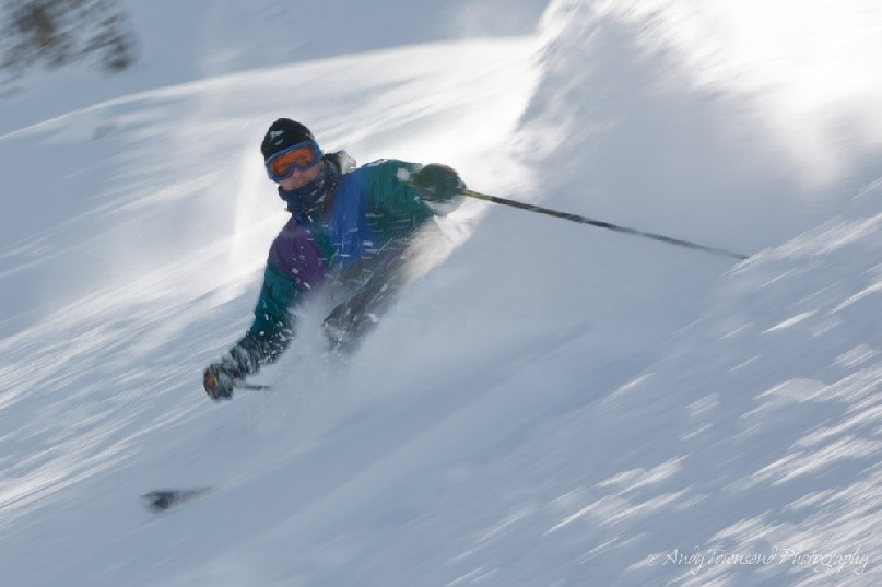 Soft powder sprays when a telemark skier turns in great snow conditions.