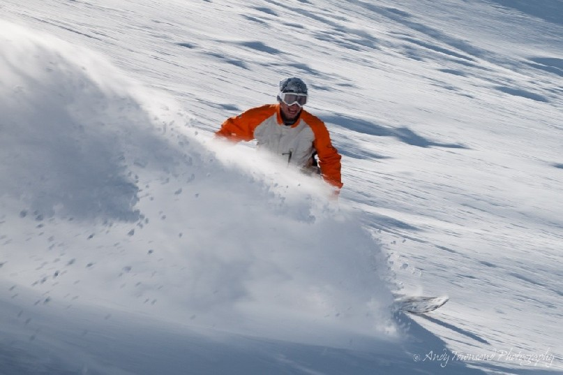 A snowboarder smiles as a plume of fresh snow sprays out.<br />