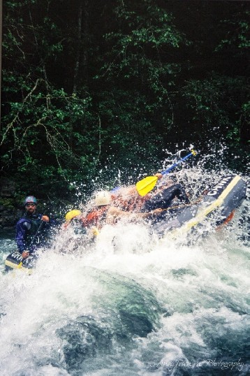 A raft guide looks cool and calm regotiating a rapid as the rest of his crew loose their grip.