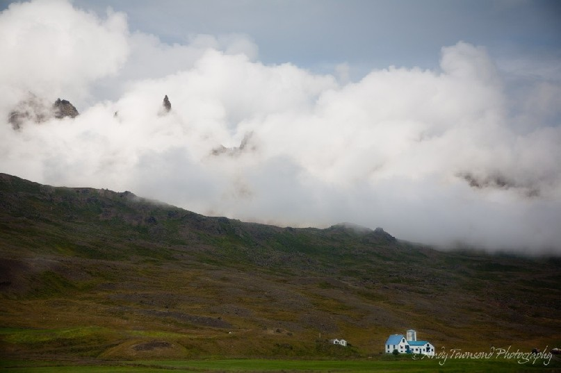 A lone farmhouse is dwarfed by the surrounding misty mountains.