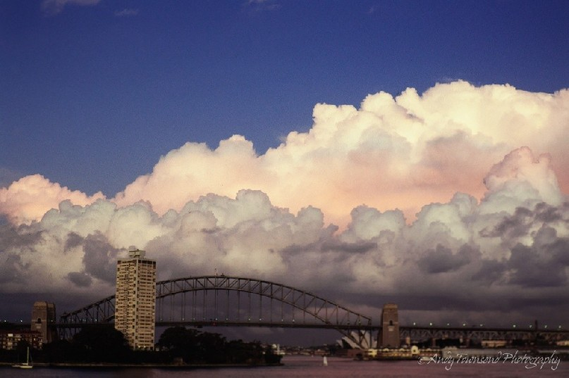 Cloud formations build from the east over Sydney harbour, the harbour bridge and opera house.