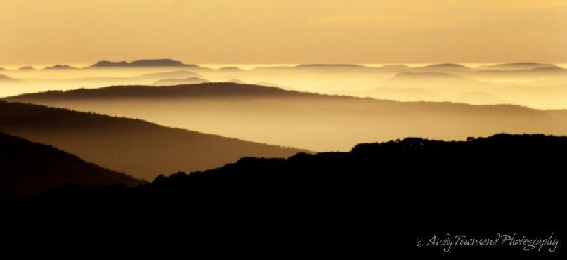 Mist hangs in the valleys between the ridgelines as the sun rises.