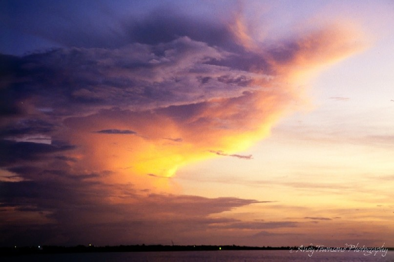 The last of the suns rays hit a building storm cloud over the city of Darwin.