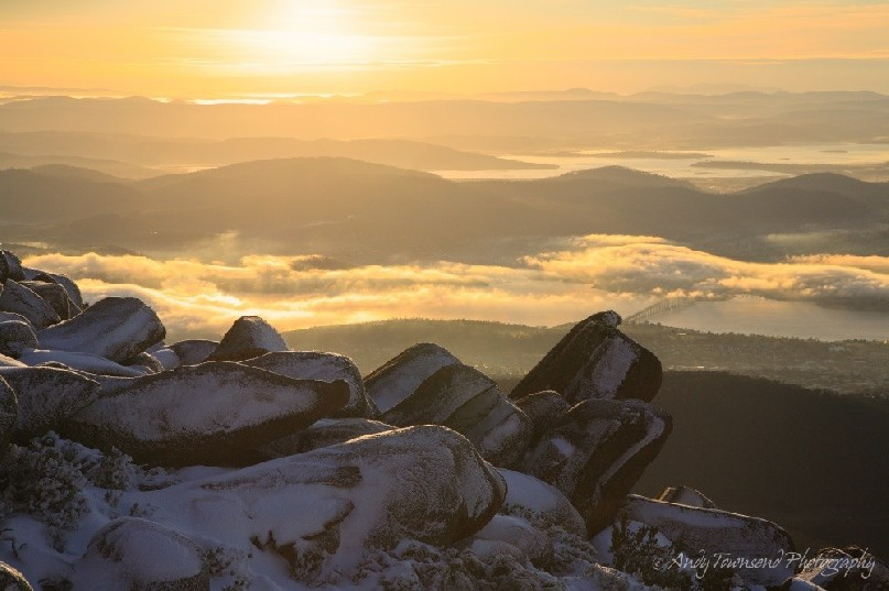 Snow lined boulders sit above a view over a misty Derwent River.