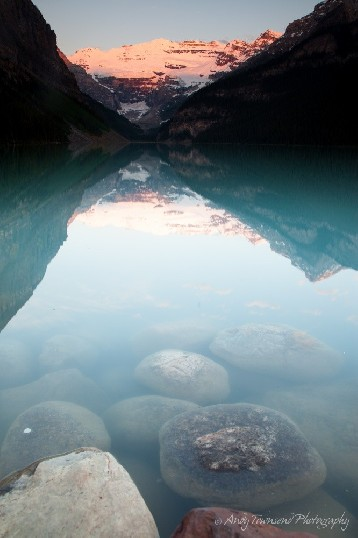 A sunrise glow hits a distant range and reflects into Lake Louise.