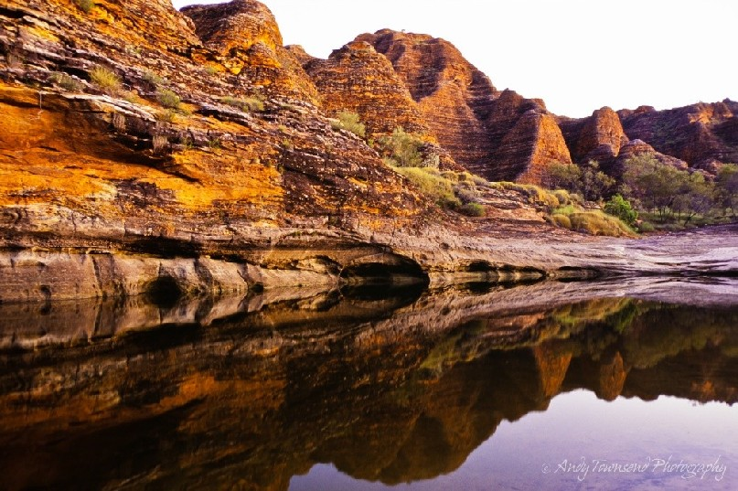 Sandstone domes reflect into a rare summer pool of water.