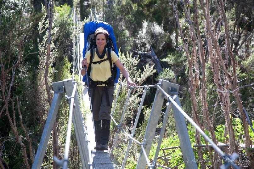 A walker crossing a suspension bridge leaving the Labyrinth area on Tasmania's Overland Track.