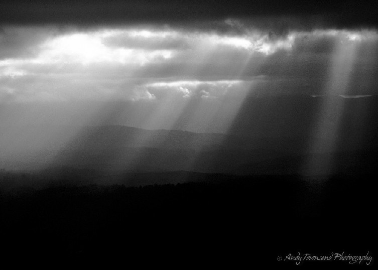 Crepuscular rays stream through gaps in clouds over  distant ridgelines.