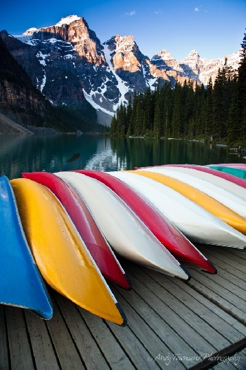 A line of colourful canoes on a jetty with Moraine Lake and the Ten Peaks in the distance.