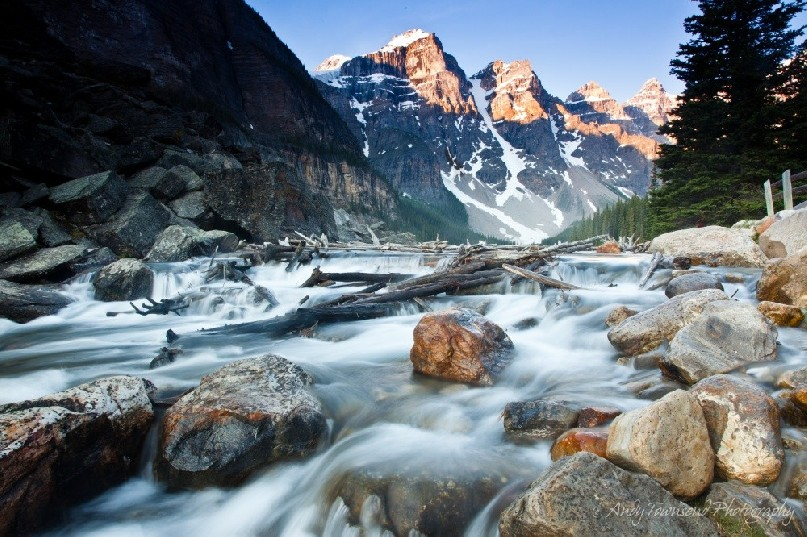 The Ten Peaks over Moraine Lake catch the morning sun while silken water flows over rocks and logs in the foreground.