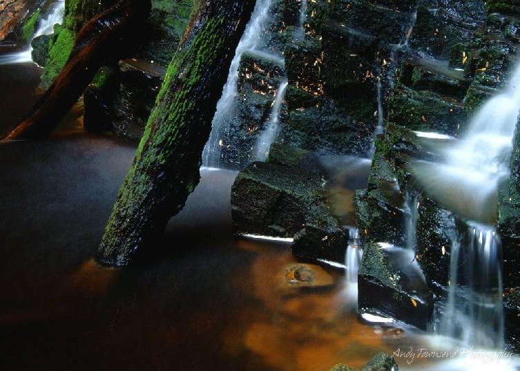 A long exposure of water falling over mossy rocks.