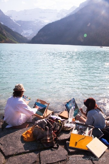 Two painters sit on the steps on the edge of Lake Louise with their equipment spread out around them.