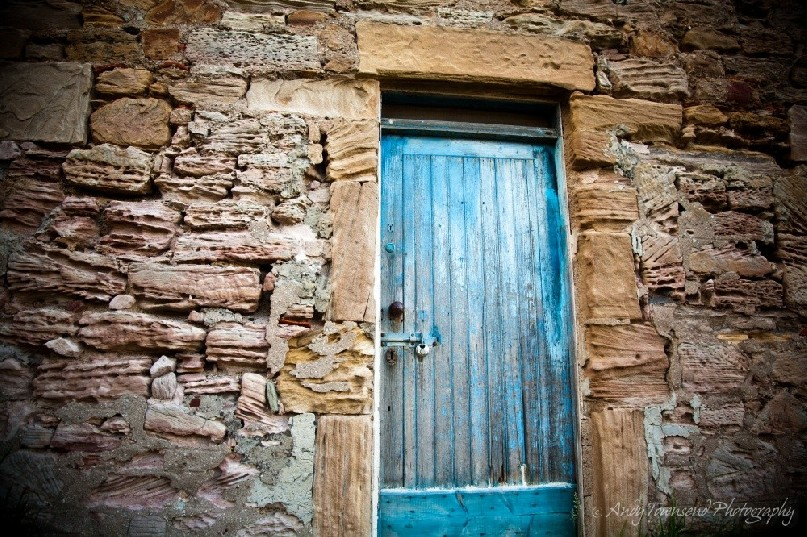 A weathered blue door sits in sharp contrast to this rough, eroded sandstone wall of this cottage.