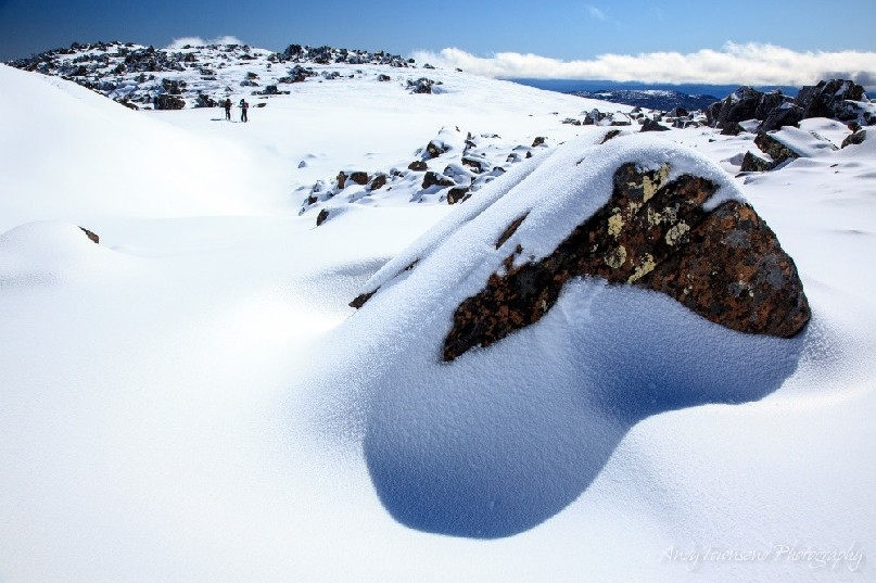 A large snow-covered boulder casts a shadow at the top of the Rodway range, with two backcountry skiers in the distance.