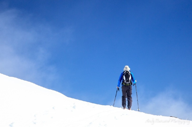 A skier makes their way across a ridgeline with a clearing blue sky above.