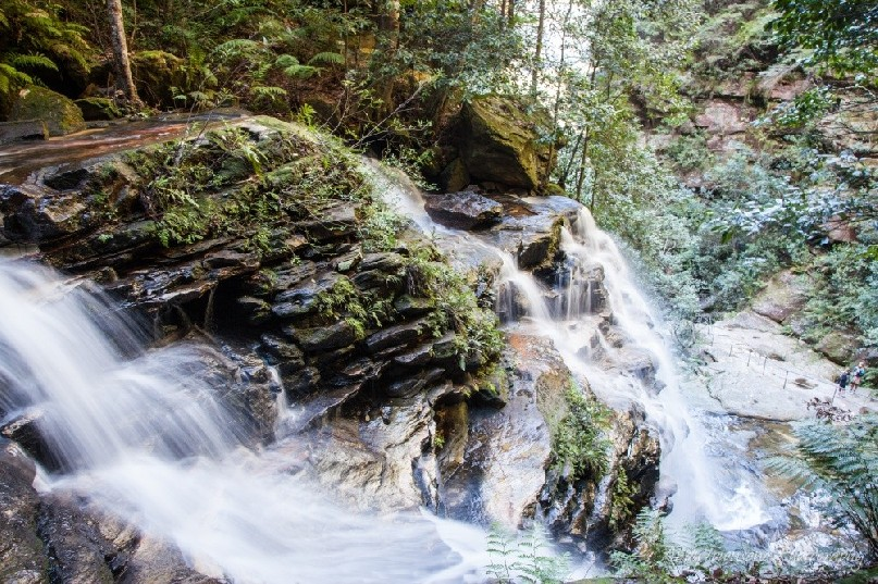 Looking down over water as it cascades down a sandstone escarpment.