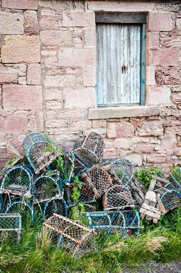 A pile of crab pots sits outside the weathered sandstone wall of this cottage.