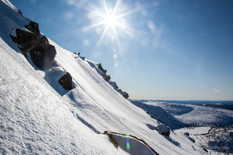 Clear blue skies and a bright sun over a distant snowshoer as they descend a step snow slope on the Rodway range.