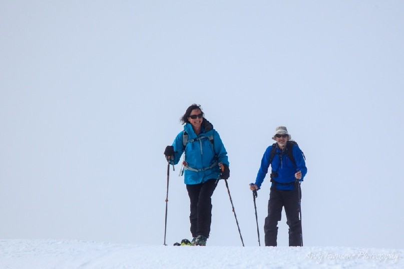 Two backcountry skiers finishing the final ascent to the ridgetop as cloud starts to move in.