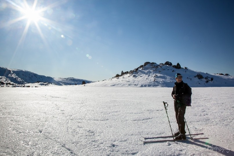 A cross-country skier pauses on the frozen Johnston tarn with a clear blue sky and bright sun behind.