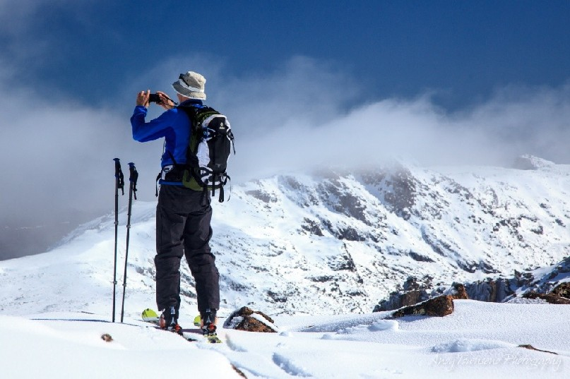 A skier pauses to photograph the mountain vista with a cloud capped mountain in the background.