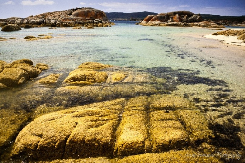 White sand and turquoise waters surround granite outcrops on Flinders Island, Tasmania, Australia.