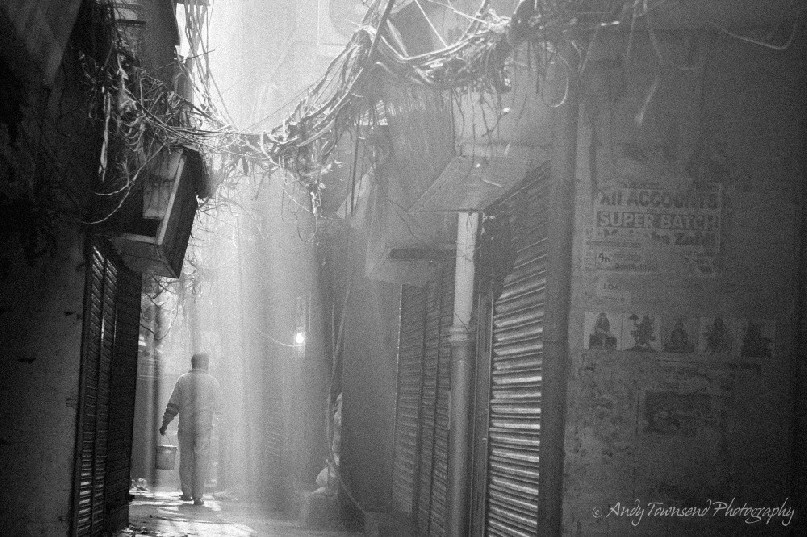 Rays of sunlight shine through dust and chaotic electrical wiring as a person walks along a narrow alleyway.