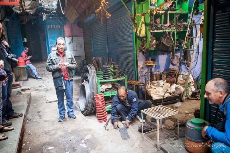 A tour guide talking next to a small metal workshop in a alley.