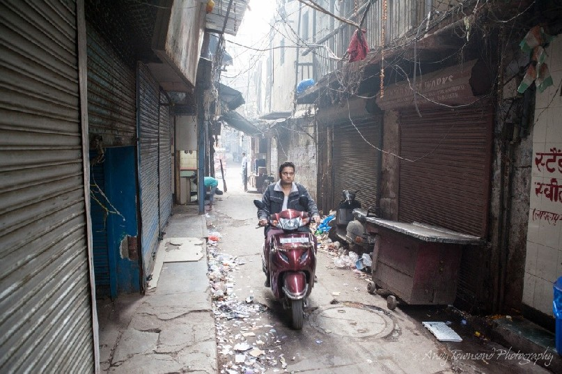 A young man rides a moped through an Old Dehli alleyway.