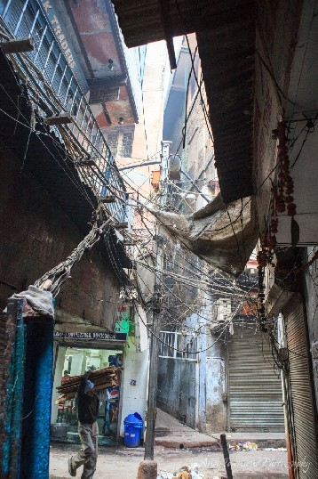 A man balancing wood over his shoulder walks into alley with a view above showing chaotic electrical wiring.