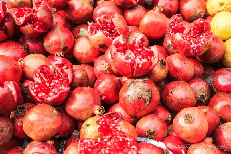 Close up of fresh pomegranates at a wholesale vegetable market.
