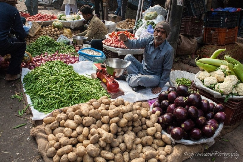 A man siting at his stall selling vegetables in a whole street market.