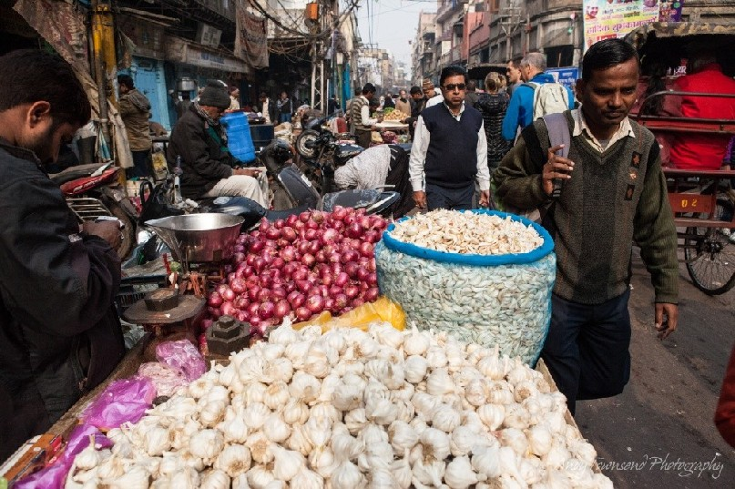 Mounds of garlic adorn this street stall at a wholesale vegetable market.
