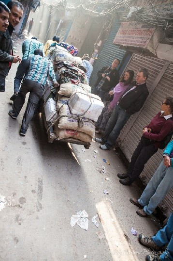 A group of men pushing a laden cart through a narrow alleyway watched on by a group of tourists.