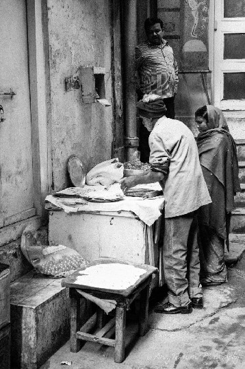 An older man and women in traditional dress making street food in alley.
