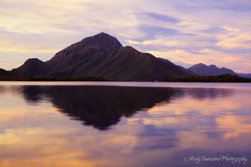 Soft evening light reflects onto the deep tannin waters of Bathurst Harbour, Southwest National Park, Tasmania.