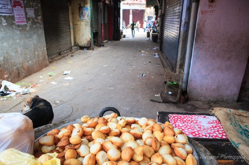 A pile of street food sits ready for customers at the end of a back alley.