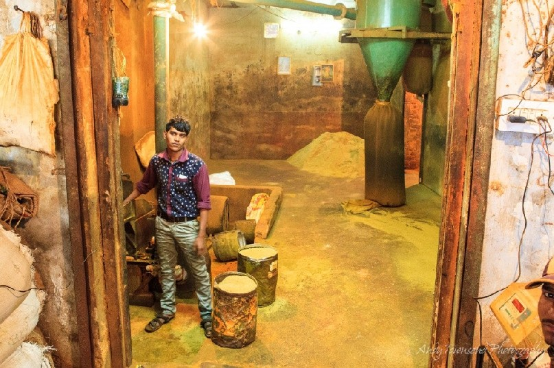 A worker operates the controls of a large spice grinder. A bag of ground coriander fills in the background.