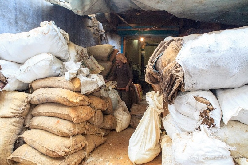 A spice worker makes his way along large bags of spice stacked under a small tarpaulin.