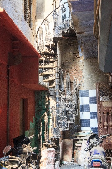 A wrought iron spiral staircase makes its way out of a dusty lane filled with old tiles and motorbikes.