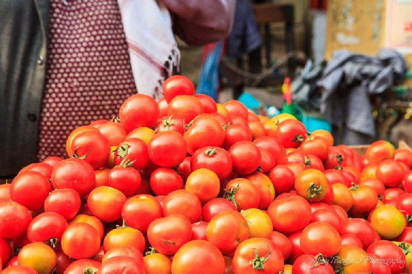 A large stack of tomatoes at a wholesale vegetable market.