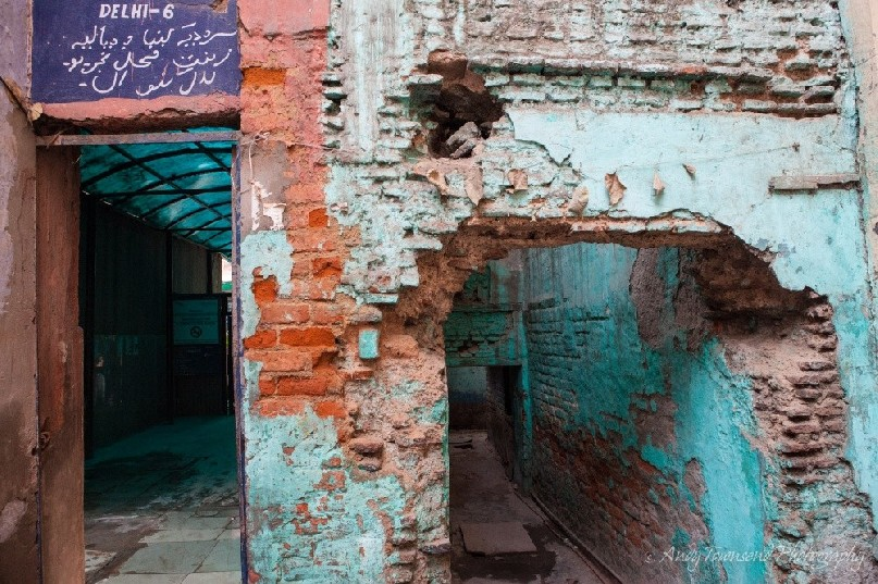Old bricks show through flaking turquoise paint at the entrance to an all-girl school.