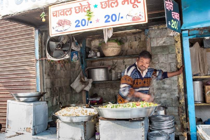 A man looks over a large pot of cooking vegetables in a rodside stall.