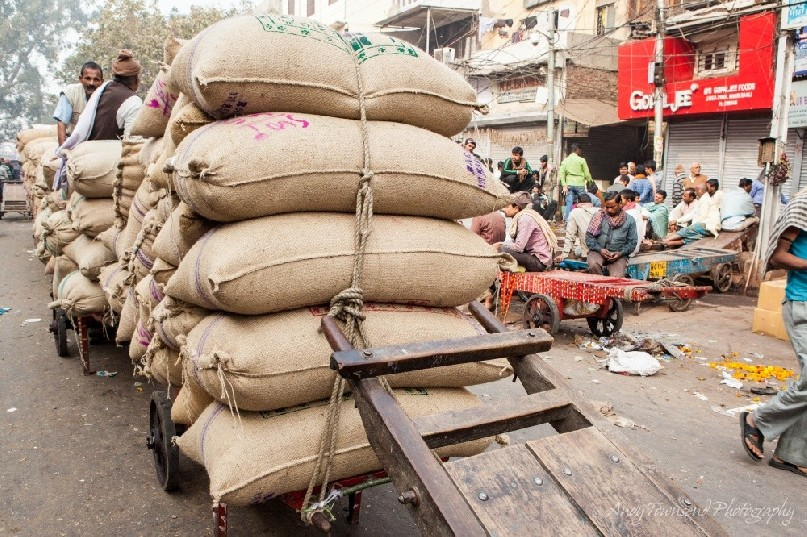 Large sacks of spice sit on wooden trolleys ready for distribution.
