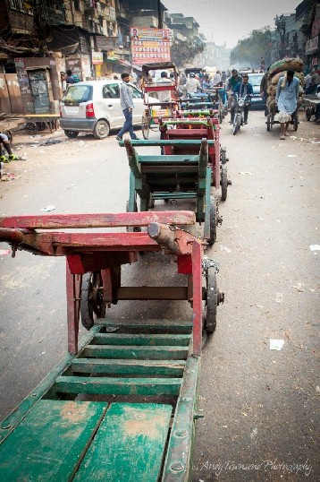 A large line of colourful wooden trolleys divides a busy street in Delhi.