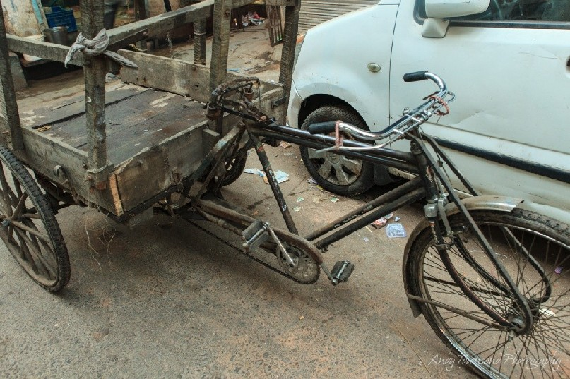 An old bike with an attached wooden cart.